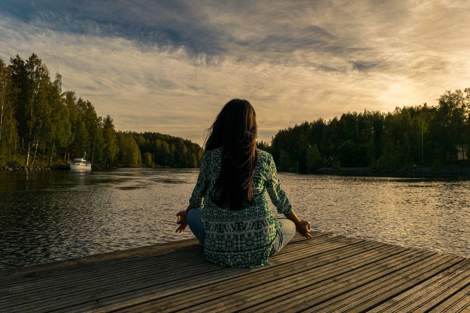 Woman sitting by the lake meditating