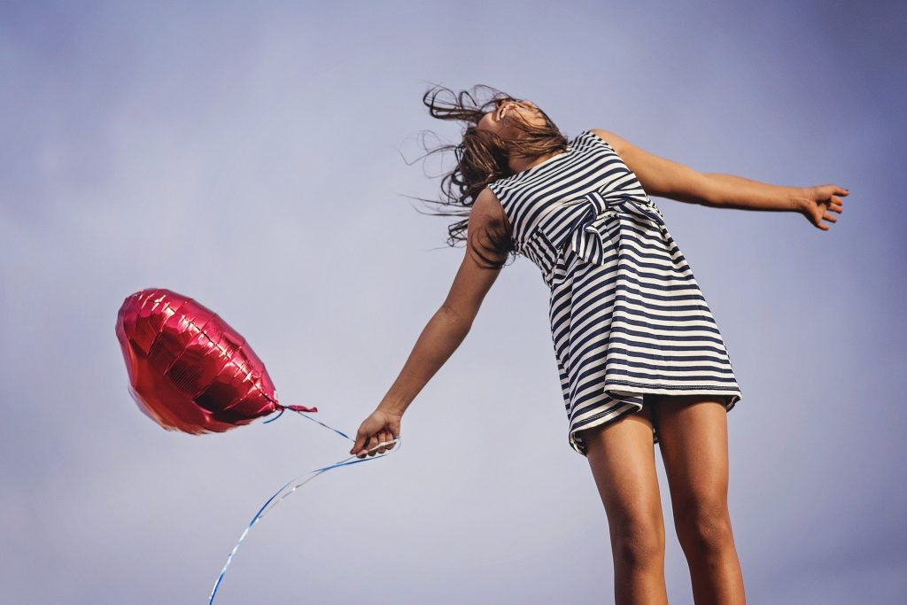 Woman holding heart balloon, arms out to the side. Her face is looking up and she has a wide mouthed mile. Blue sky background. She is expressing joy and happiness of being unstuck.