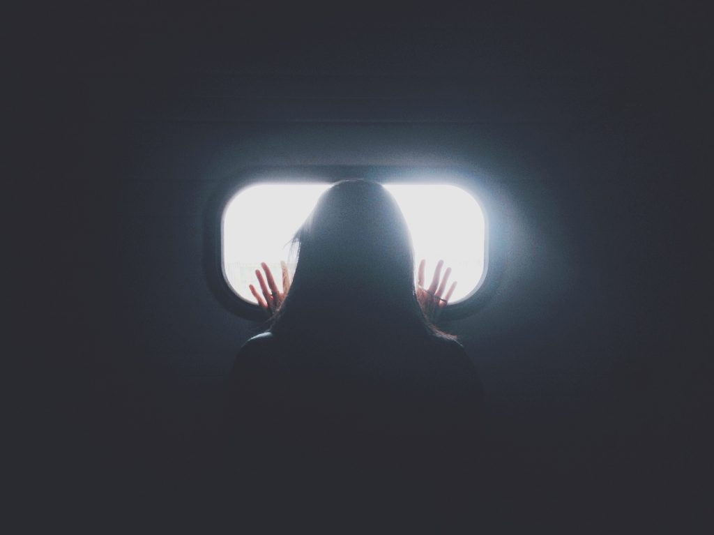 Back of womans head.looking out of a small window. Her hands are up on the glass and light is shinning through the window. Showing her feeling trapped.